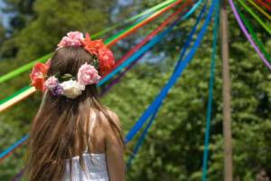 Girl with flower crown next to May Pole